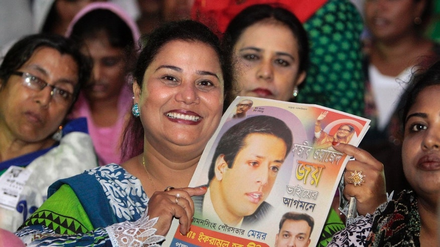 In this Sunday, Sept. 15, 2013 photo, a Bangladesh Awami League woman supporter holds a poster of Sajeeb Wazed Joy, 42, the son of Prime Minister Sheikh Hasina, at an election campaign rally in Mymensingh, near Dhaka, Bangladesh. Political observers in Bangladesh say that given a few years Joy or Tarique Rahman, the 45-year-old son of opposition leader Khaleda Zia, could become prime minister of Bangladesh, which has been ruled by their two families since the country's 1971 independence from Pakistan. Joy and Rahman have emerged as the country's most powerful political heirs. (AP Photo/A.M. Ahad)