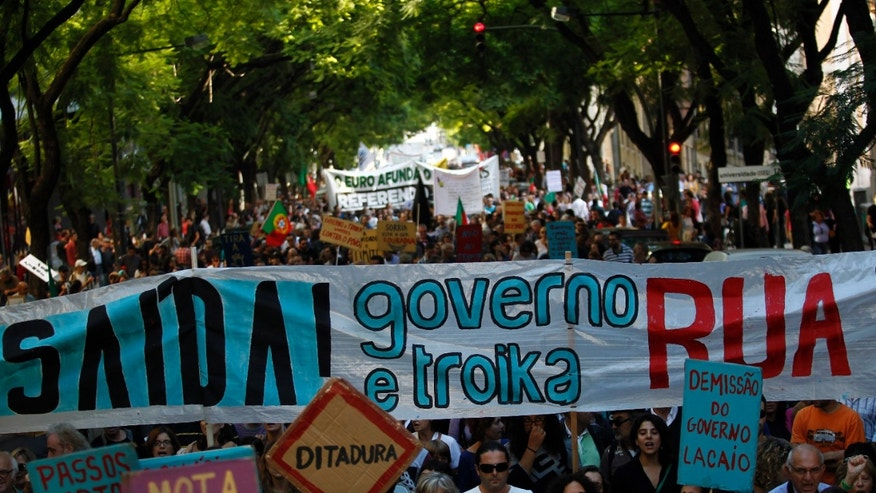 """People, some of them holding a large banner that reads in Portuguese: """"There is a Way! Government and Troika Out!"""", march towards the Portuguese parliament during a demonstration against austerity measures taken by the Portuguese government in exchange for an euro 78 billion (US$ 107.6 billion) bailout needed in 2011, in Lisbon, Saturday, Oct. 26, 2013. Others placards read in Portuguese: """"Dictatorship"""" and """"Resignation of the lackey government"""". (AP Photo/Francisco Seco)"""