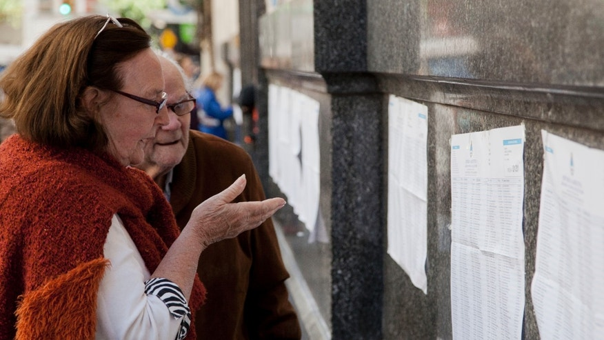 People look for their names in electoral rolls at a polling station during mid term legislative elections  in Buenos Aires, Argentina, Sunday, Oct. 27, 2013. Sunday's run-up to congressional elections will decide how much control President Cristina Fernandez will have over Argentine politics during the final two years of her presidency. (AP Photo/Eduardo Di Baia)