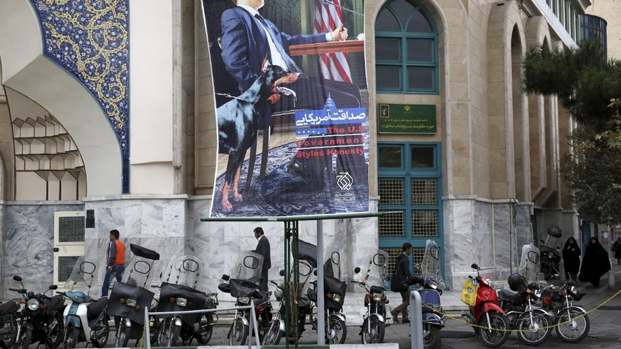 "A poster depicting an American negotiator wearing a suit jacket and tie at a negotiating table and a dog to his side is displayed in Palestine square, Tehran, Iran, Sunday, Oct. 27, 2013. Iranian President Hassan Rouhani has described his outreach to the U.S. as part of a ""new era'' and a chance to put the nuclear standoff with the West to rest. (AP Photo/Ebrahim Noroozi)"