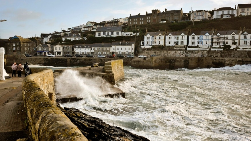 People walk along a path as waves crash onto a seawall protecting the harbor of Porthleven, Cornwall, southwest England, Sunday, Oct. 27, 2013. Forecasters say a severe storm will hit the southern half of Britain later Sunday, bringing heavy rains and gusts of 60 to 80 miles per hour (100 to 130 kilometers per hour, with the potential to cause widespread and severe disruption from falling trees, power cuts and flooding. (AP Photo/PA, Ben Birchall) UNITED KINGDOM OUT, NO SALES, NO ARCHIVE