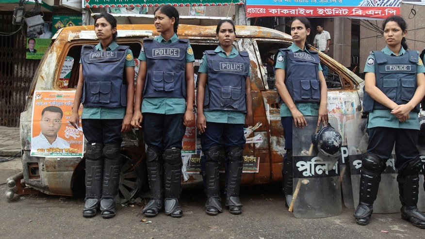 Bangladeshi riot policewomen stand guard in front of a burnt-out car which was set afire by opposition supporters previously, outside the office of the main opposition Bangladesh Nationalist Party (BNP) during a general strike in Dhaka, Bangladesh, Sunday, Oct. 27, 2013. The protest is aimed at forcing Prime Minister Sheikh Hasina to quit and form a caretaker government made up of people from outside political parties to oversee an election due by early next year. The shutdown is to continue until Tuesday night. (AP Photo/A.M. Ahad)
