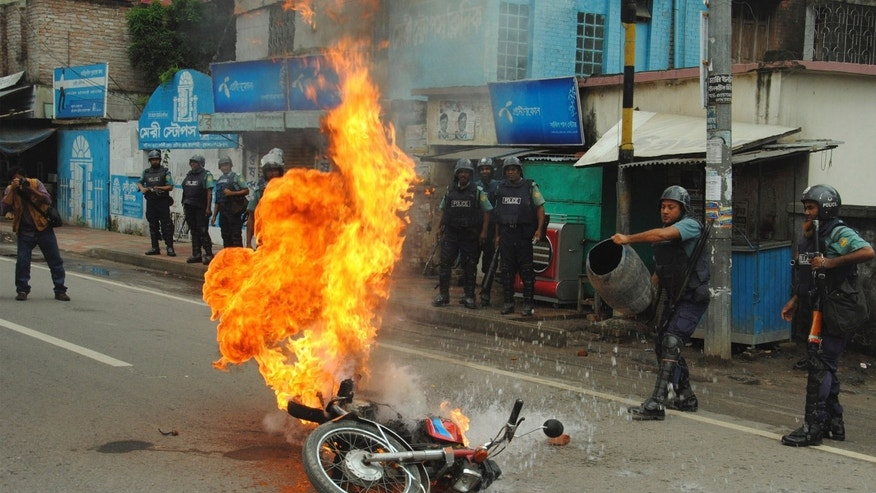 Bangladeshi police officers try to douse the flames on a motorcycle allegedly ignited  by opposition activists during a general strike in Rajshahi, outskirts of Dhaka, Bangladesh, Sunday, Oct. 27, 2013.  Police and supporters of Bangladesh's ruling party clashed Sunday with opposition supporters, leaving fatalities and scores injured in different parts of the country as opposition parties tried to enforce a three-day nationwide general strike. (AP Photo)