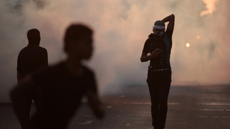 An anti-government protester, right, covers his face from tear gas fired by riot police during clashes following a traditional third-day mourning gathering for Ali al-Sabagh, 17, in Bani Jamra, Bahrain, on Saturday, Oct. 26, 2013. Authorities said Al-Sabagh was killed when an explosive device he was carrying detonated prematurely. (AP Photo/Hasan Jamali)