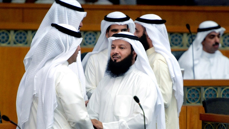 In this Wednesday, Sept. 4, 2013 photo, Kuwaiti Islamist AP Ahmed Al Azmi, center, speaks with lawmakers during a National Assembly session in Kuwait. One of the most traditional pleasures of the Middle East _ leisurely puffing on a water pipe filled with aromatic tobacco _ has become ensnared in another of the region's familiar backdrops: Islamic conservatives decrying what they see as liberal decadence. (AP Photo/Gustavo Ferrari)