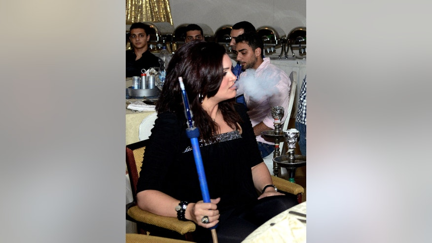 In this Monday, July 22, 2013 photo, an Arab woman smokes a water pipe during the holy Islamic month of Ramadan at a restaurant  in Kuwait. One of the most traditional pleasures of the Middle East, leisurely puffing on a water pipe filled with aromatic tobacco _ has become ensnared in another of the region's familiar backdrops: Islamic conservatives decrying what they see as liberal decadence. (AP Photo/Gustavo Ferrari)