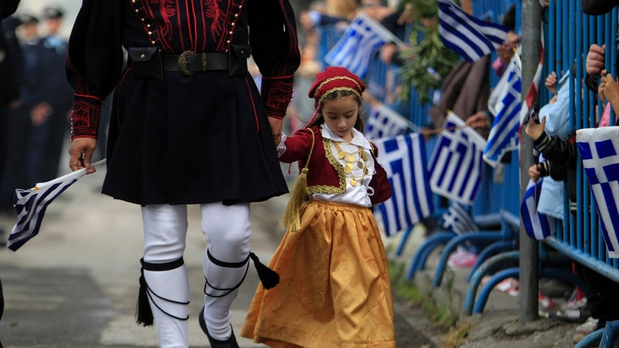 A girl dressed in a traditional costume holds the hand of a man in traditional military uniform during a parade, in the northern port city of Thessaloniki, Greece,  on Monday, Oct. 28, 2013. A military parade commemorating Greece's entry into World War II, 73-years ago, has been held without incident as thousands of Greek police were deployed to keep any anti-austerity protesters at bay.  (AP Photo/Nikolas Giakoumidis)