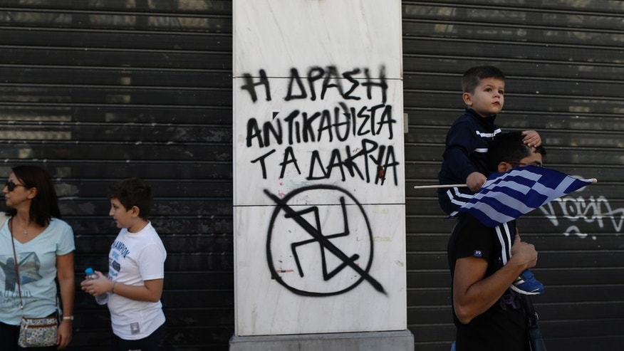 "A child holds a Greek flag as he passes with his father next a graffiti depicting an anti Nazi Symbol and reading in Greek "" Action replace tears"" during a parade commemorating Greece's entry in World War II in 1940, in central Athens, on Monday, Oct. 28, 2013.(AP Photo / Petros Giannakouris)"