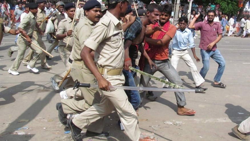 People thrash a man whom the police detain and take away for questioning after a bomb blast outside the venue of a political rally in Patna, India, Sunday, Oct.27, 2013. A series of small bomb blasts killed some people and injured dozens Sunday just hours before a campaign rally by the country's main opposition prime ministerial candidate Narendra Modi. (AP Photo/Aftab Alam Siddiqui)