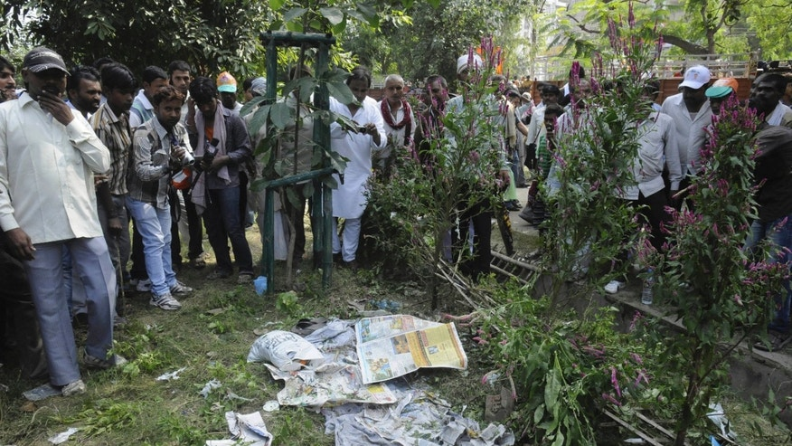 People gather very close to an unexploded  bomb, hidden beneath newspapers before it was defused by officials outside the venue of a political rally in Patna, India, Sunday, Oct. 27, 2013. A series of small bomb blasts killed some people and injured dozens Sunday just hours before a campaign rally by the country's main opposition prime ministerial candidate Narendra Modi. (AP Photo/Aftab Alam Siddiqui)