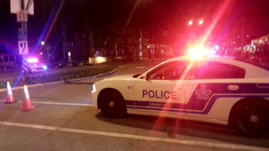 Oct. 27, 2013: A Montreal police car blocks off a street in a residential area near Trudeau International Airport after the discovery of a potential explosive device found in the carry-on luggage of a 71-year-old man who was headed to Los Angeles. The man has been detained.