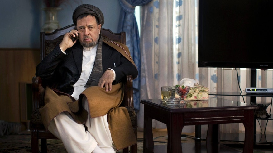 Mohammed Mohaqiq, a senior member of Afghanistan's high peace council and vice presidential candidate in next year's elections, talks on the phone in his office in Kabul, Afghanistan, Sunday, Oct 27, 2013. The high peace council has been designated by Afghan President Hamid Karzai to negotiate peace with the Taliban but Mohaqiq says the council has little influence. (AP Photo/Anja Niedringhaus)