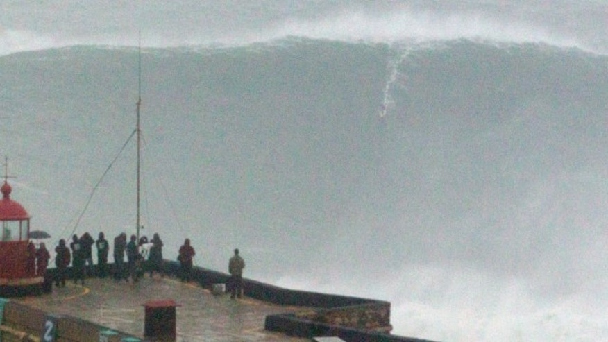 Oct. 28 2013: Brazilian surfer Carlos Burle rides a big wave at the Praia do Norte, north beach, at the fishing village of Nazare in Portugal's Atlantic coast.