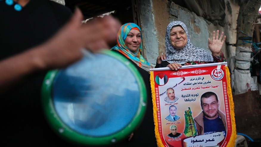 """Tamam Masoud, 70, mother of Omar, 40, who was arrested in May 1993 for killing an Israeli lawyer, greets her neighbors while holding a banner in front of her family house at Shati Refugee Camp in Gaza City, Tuesday, Oct. 29, 2013. Masoud is one of 26 Palestinian prisoners Israel approved to release, in the second batch to be freed since August under the terms of renewed US-brokered peace talks. It is the second of four planned releases of the longest-serving Palestinian prisoners held by Israel in the coming months. The Arabic on the banner reads, """"On the 20th anniversary of his arrest, PFLP (the Popular Front for the Liberation of Palestine) salute comrade prisoner Omar Masoud, Freedom for prisoners."""" (AP Photo/Adel Hana)"""