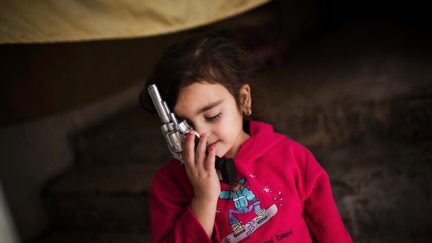 In this Monday, Oct. 21, 2013 photo, a Syrian refugee girl plays with a toy gun at her family's house in Zarqa, Jordan's industrial center where thousands of Syrian refugees are living, northeast of the capital Amman. More than 420,000 Syrian refugees have settled in Jordan's cities, struggling for survival on U.N. foods stamps and straining the meager resources of a country that absorbed millions of exiles from the region's hotspots in the past. (AP Photo/Manu Brabo)