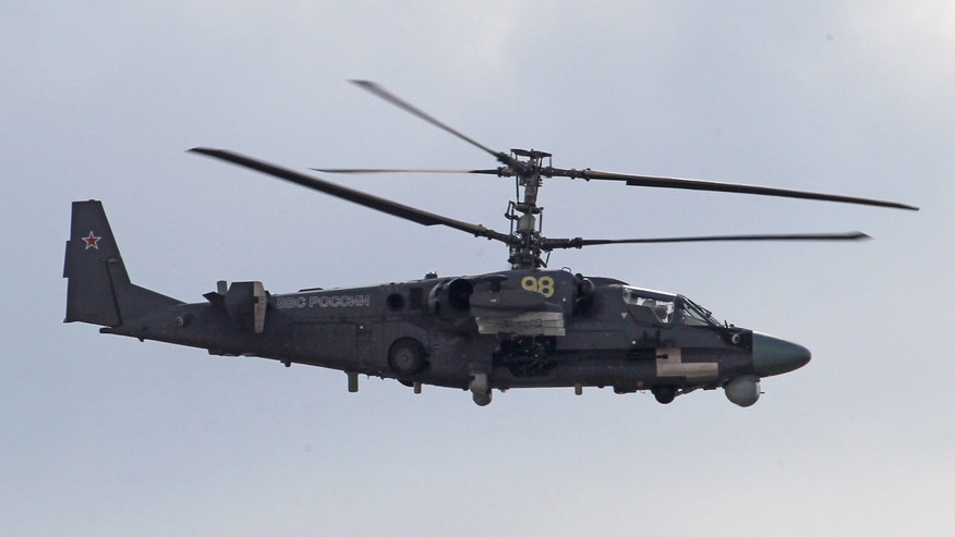 FILE -  In this Sunday, Aug. 12, 2012 file photo, a Russian made Ka-52 Alligator attack helicopter in flight during a celebration marking the Russian air force's 100th anniversary in Zhukovsky, outside Moscow, Russia. A Ka-52 crashed on Moscow's outskirts Tuesday, Oct. 29, 2013, during a test flight. Both crew members bailed out safely and there was no damage on the ground. (AP Photo/ Mikhail Metzel, file)