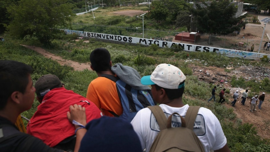 Central American immigrants arrive on top of a freight train to the Hermanos en el Camino immigrant shelter on August 6, 2013 in Ixtepec, Mexico.