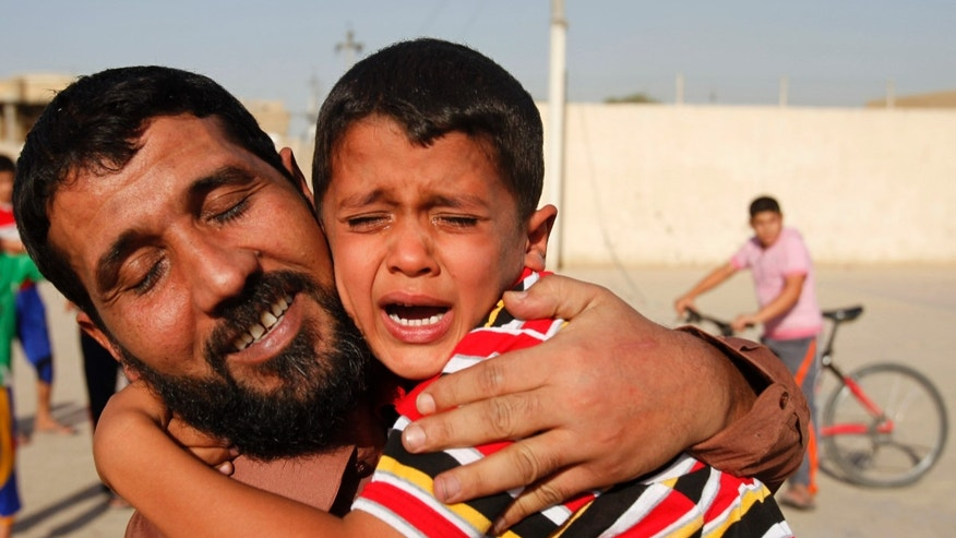 FILE - In this file photo taken on Sept. 27, 2009, file, Haidar Talib, a member of a militant group called Asaib Ahl al-Haq, or League of the Righteous, embraces his 4-year-old son Mustafa as he is released from U.S. military custody in Baghdad, Iraq. The wave of attacks by al-Qaida and Sunni extremists that has killed thousands of Iraqis in 2013 so far, most of them Shiites, is provoking ominous calls from Shiite leaders to take up arms in self-defense. Iraq's Shiite prime minister, Nouri al-Maliki, who will meet with U.S. President Barack Obama on Friday, Nov. 1, 2013, said he wants American help in quelling the violence. (AP Photo/Khalid Mohammed, File)