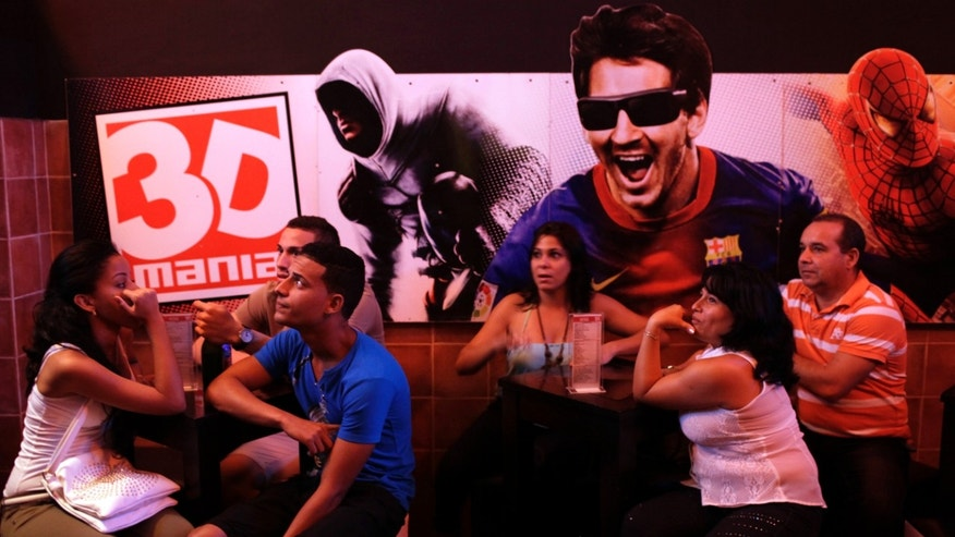 "People wait to see a movie next to a image of Barcelona soccer player Lionel Messi at a private movie theater called ""3D Mania"" in Havana, Cuba, Tuesday, Oct. 29, 2013. Cuban entrepreneurs have quietly opened dozens of backroom video salons over the last year, seizing on ambiguities in licensing laws to transform cafes and children's entertainment parlors into a new breed of private business unforeseen by recent official openings in the communist economy. (AP Photo/Franklin Reyes)"