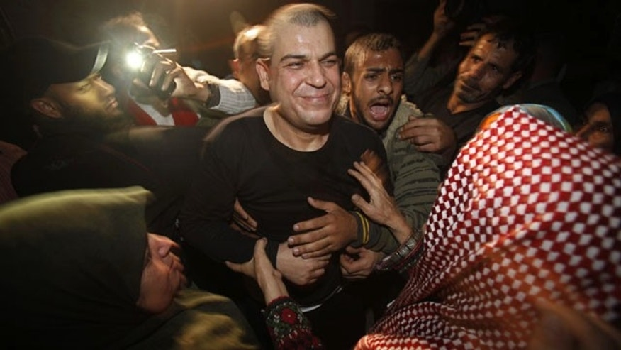 October 30, 2013: A released Palestinian prisoner, Omar Masoud, 40, center, who was arrested in May, 1993 for killing an Israeli lawyer, smiles to his mother Tamam Masoud, 70, right, upon his arrival to his family house in Shati Refugee Camp. (AP Photo)
