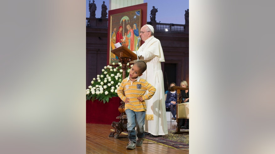 In this Saturday, Oct. 26, 2013 photo provided by the Vatican newspaper L'Osservatore Romano, Pope Francis reads his message as a young boy plays in front of him on the stage during an audience with families in St. Peter's Square, gathered for the Pontifical Council for the Family's plenary assembly, at the Vatican, Saturday, Oct. 26, 2013. A young boy, part of a group of children sitting around the stage where the pontiff was delivering his message to families, played around Pope Francis as he continued delivering his speech, occasionally patting the boy's head. (AP Photo/L'Osservatore Romano)
