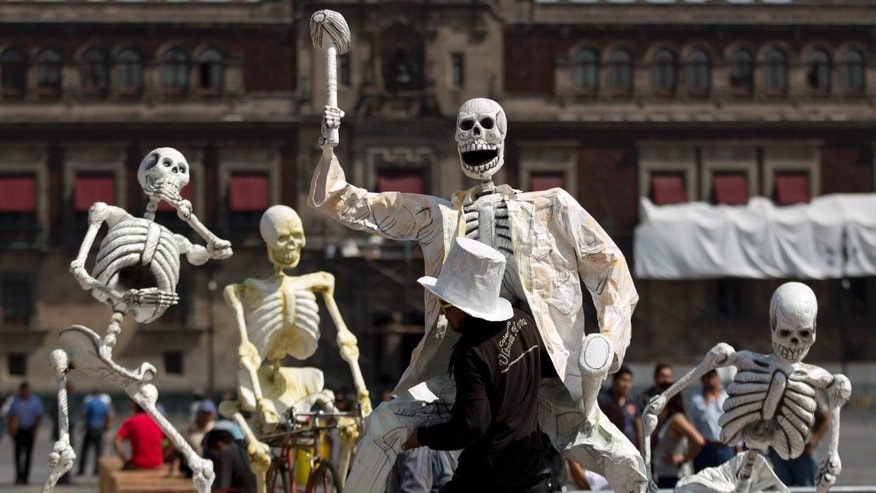 A man carries an artwork of a skeleton in preparation for the Day of the Dead celebrations in Mexico City's Zocalo, Tuesday, Oct. 29, 2013.  Mexicans celebrate Day of the Dead to honor deceased loved ones, a tradition that coincides with All Saints Day and All Souls Day on Nov. 1 and 2. (AP Photo/Eduardo Verdugo)