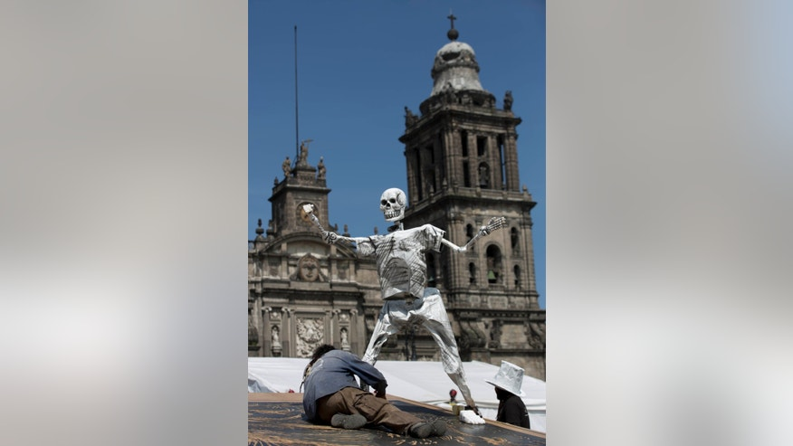 An artist works on an artwork of a skeleton in preparation for the Day of the Dead celebrations in Mexico City's Zocalo, Tuesday, Oct. 29, 2013.  Mexicans celebrate Day of the Dead to honor deceased loved ones, a tradition that coincides with All Saints Day and All Souls Day on Nov. 1 and 2. (AP Photo/Eduardo Verdugo)
