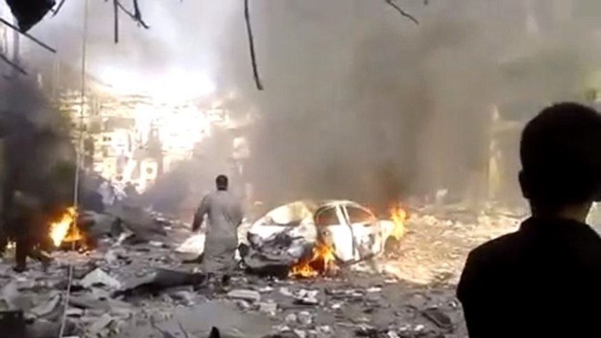 Oct. 14, 2013: This image made from citizen journalist video posted by the Shaam News Network, which is consistent with other AP reporting, shows the aftermath of a car bomb attack on a market in the town of Darkoush in Idlib province, Syria.