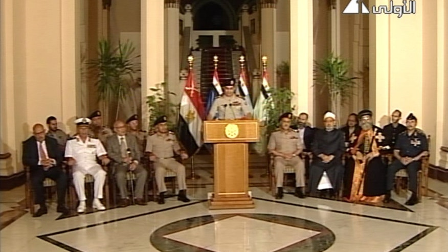 FILE - In this Wednesday, July 3, 2013 file photo made from video, Lt. Gen. Abdel-Fattah el-Sissi, center, flanked by military and civilian leaders in including reform leader Mohamed ElBaradei, far left, Tamarod leader Mahmoud Badr, second left, Grand Sheik of Al-Azhar, Ahmed el-Tayeb, third from right, and Pope Tawadros II, second from right, as he addresses the nation on Egyptian State Television. Under President Mohammed Morsi, his Islamist allies pushed through a constitution that alarmed many Egyptians with its new, stronger provisions for implementing Islamic Shariah law and carving out extensive power for the military. Now after Morsi's ouster, it is the turn of liberal and secular politicians to amend the charter, but they are balking at reversing those changes, caught up in the country's stormy politics.  (AP Photo/Egyptian State Television, File)