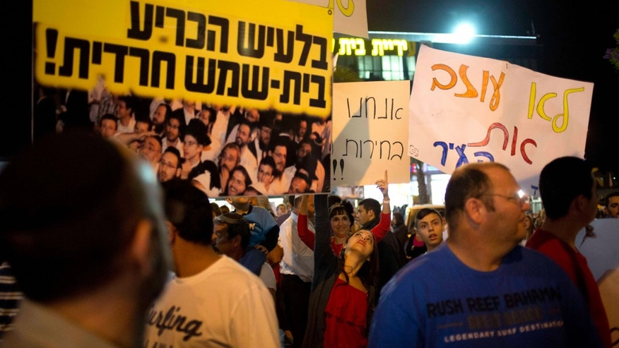 In this Tuesday, Oct. 29, 2013, photo, Israeli secular and moderate religious residents of Beit Shemesh protest during a demonstration demanding a new vote in the mayoral election and even suggesting the city be split in two claiming the election was stolen, in Beit Shemesh, Israel. After a contentious mayoral election between secular and ultra-Orthodox rivals, this deeply divided city has become a flashpoint for a religious struggle that is threatening to tear Israel apart. The protests go far beyond the alleged election fraud. They cut at the very nature of Israel as it tries to maintain its character as both a Jewish state and a pluralistic democracy. (AP Photo/Ariel Schalit)