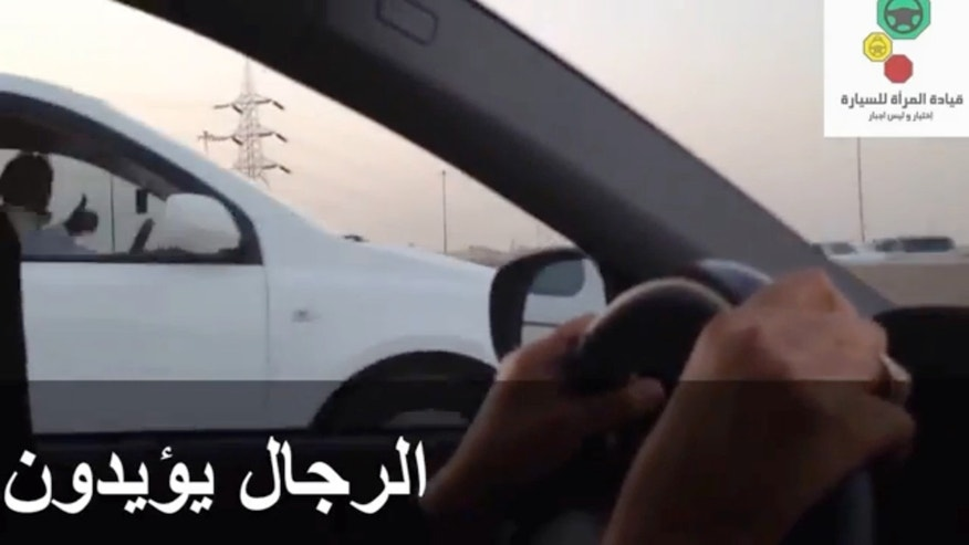 "This image made from video taken on Oct. 26, 2013 provided by the Oct. 26 driving campaign, which has been authenticated based on other AP reporting, shows a man in a car giving a thumbs-up to a woman driving in Saudi Arabia during a day of protest by women who got behind the wheel to defy a driving ban in the kingdom. Arabic reads ""men are supporting."" Men risking careers and livelihoods are working quietly behind the scenes to help steer a campaign to grant Saudi women the right to drive. They have been filming women flouting the kingdom's driving ban, uploading videos, posting on Facebook and Twitter, teaching their sisters and wives how to drive, and riding in packs next to female drivers to protect them from harassment. But the arrest this week of an outspoken male reformer has sent chills among activists who fear authorities are ramping up pressure on male relatives and supporters to clamp down on the effort. (AP Photo/Oct. 26 Driving Campaign)"