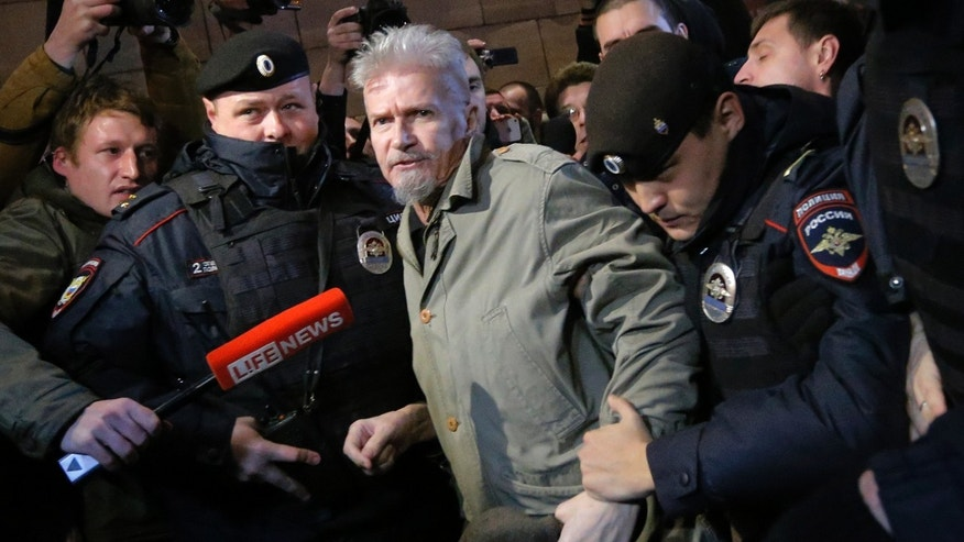 Police detain opposition leader Eduard Limonov during an unsanctioned opposition rally in Moscow, Russia, Thursday, Oct. 31, 2013. Limonov is an avant-garde author and longtime political fringe figure. He and his supporters try to hold demonstrations on the 31st day of every appropriate month. The date choice refers to the 31st Article of the Russian constitution, which guarantees the right of assembly. (AP Photo/Dmitry Lovetsky)