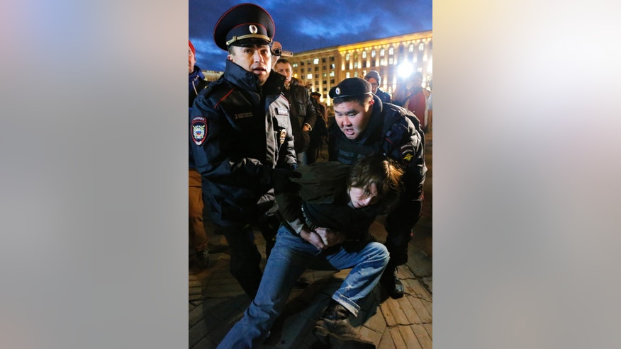 Police detain an opposition supporter during an unsanctioned opposition rally in downtown Moscow, Russia, Thursday, Oct. 31, 2013. The Russian opposition protests on the 31st of each month are a nod to the 31st article of the Russian constitution, which guarantees the right of assembly. (AP Photo/Dmitry Lovetsky)