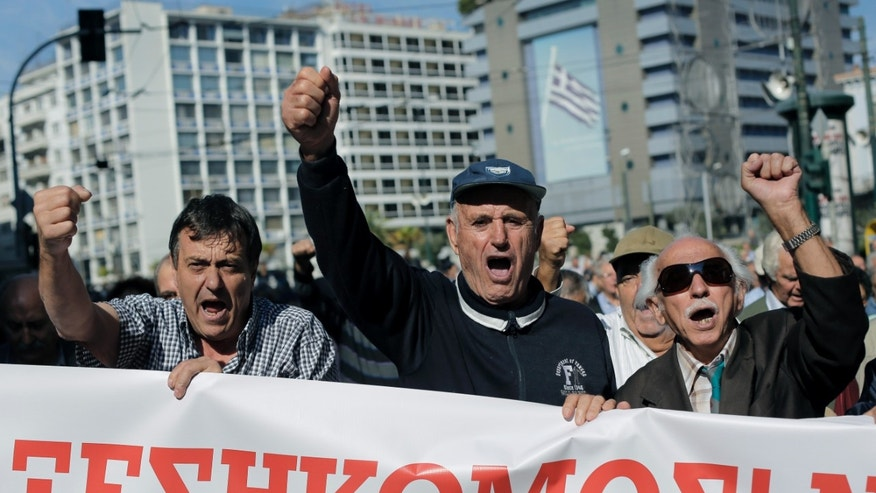 "Pensioners hold a banner which reads in Greek ""Uprising"" as they chant anti austerity slogans during a protest in central Athens, on Thursday, Oct. 31, 2013. Elderly Greeks have faced successive pension cuts since Greece began relying on international rescue loans in 2010, and have also been hard hit by health care cuts. (AP Photo/Petros Giannakouris)"