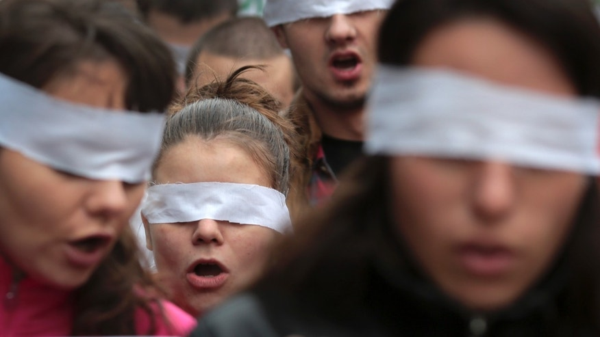 Blindfolded protestors shout anti-government slogans during a demonstration in central Sofia, Friday, Nov. 1, 2013, demanding the dissolution of Parliament and calling for new elections. Several hundred students, who have occupied many universities for a week, were joined on Friday by teachers in their demands for an effective nationwide strike. (AP Photo/Valentina Petrova)