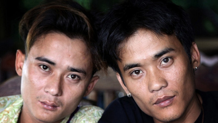 "In this Sept. 26, 2013 photo, Johnny, left, and his twin brother Luther Htoo pose for photos after their reunion at a restaurant in Sangkhlaburi district of Kanchanaburi province, western Thailand. When they were kids, Johnny and Luther Htoo were bulletproof and invulnerable to land mines - or so went the story that briefly made them famous as hundreds of guerrillas followed and even worshipped them in the southeastern jungles of Myanmar. Today, well over a decade later, their ""God's Army"" is no more, and the twins' greatest accomplishment may be that both are still alive. (AP Photo/Apichart Weerawong)"