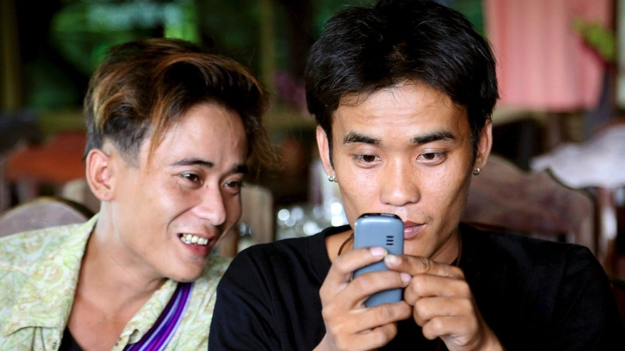 "In this Sept. 26, 2013 photo,  Johnny, left, watches his twin brother Luther Htoo play a game on his mobile phone after their reunion at a restaurant in Sangkhlaburi district of Kanchanaburi province, western Thailand. Johnny and Luther Htoo, who grabbed headlines more than a decade ago as 12-year-old twins leading a small band of anti-government guerrillas in Myanmar, were reunited at this border town in Thailand. When they were kids, they were bulletproof and invulnerable to land mines - or so went the story that briefly made them famous as hundreds of guerrillas followed and even worshipped them in the southeastern jungles of Myanmar. Today, well over a decade later, their ""God's Army"" is no more, and the twins' greatest accomplishment may be that both are still alive. (AP Photo/Apichart Weerawong)"