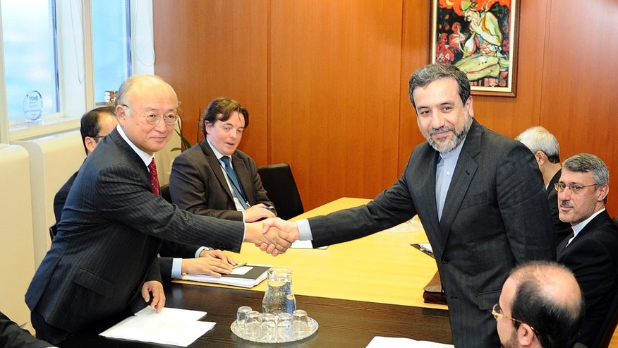 Iran's deputy Foreign Minister Abbas Araghchi, right, and Director General of the International Atomic Energy Agency, IAEA, Yukiya Amano shake hands prior to a meeting at the International Center in Vienna, Austria on Monday, Oct. 28, 2013. The meeting was held before agency experts meet Iranian diplomats in a renewed push to probe suspicions that Tehran worked on nuclear arms. (AP Photo/Hans Punz)