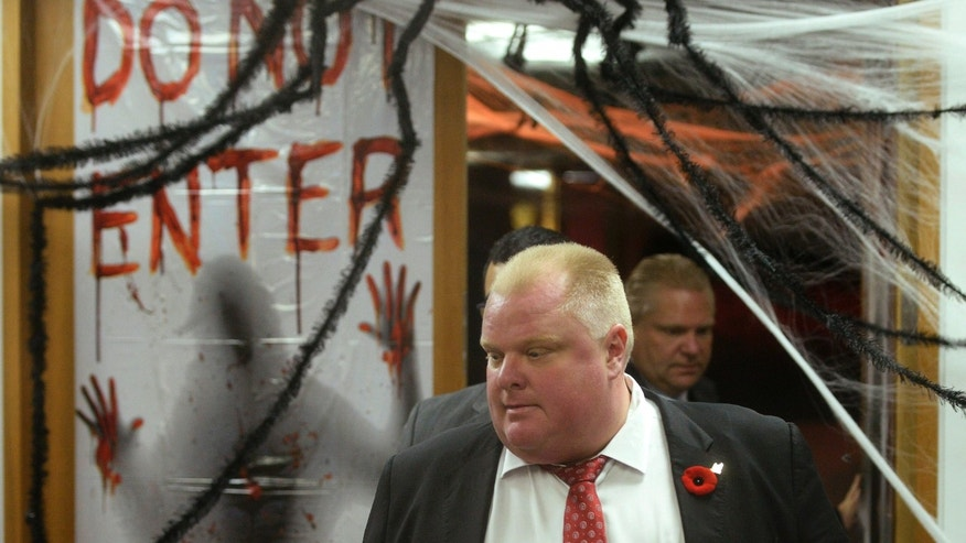 Mayor Rob Ford walks past Halloween decorations on his way to talk to media at City Hall in Toronto on Thursday, Oct. 31, 2013. Ford says he has no reason to step down despite police confirmation that they have seized a video that appears to show him smoking a crack pipe. (AP Photo/The Canadian Press, Frank Gunn)