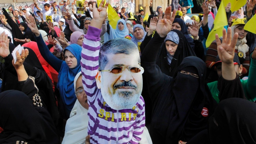 A child of a supporter of Egypt's ousted President Mohammed Morsi wears a mask with the leader's picture as people raise their hands with their four fingers, which has become a symbol of the Rabaah al-Adawiya mosque, where Morsi supporters held a sit-in for weeks in August that was violently dispersed later, during a protest in Cairo, Egypt, Friday, Nov. 1, 2013. Some 20,000 police officers and soldiers will guard the upcoming trial of Egypt's toppled president on Nov. 4, as Islamist opponents plan massive protests that may spark more turmoil in the country. (AP Photo/Amr Nabil)