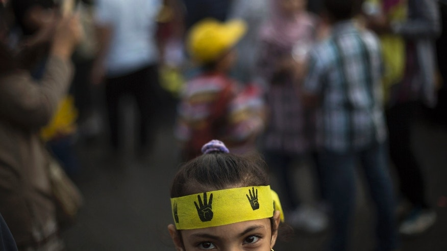 An Egyptian girl attends a protest by supporters of Egypt's ousted President Mohammed Morsi, in Nasr City in Cairo, Egypt, Friday Nov. 1, 2013. Her headband bears the four-fingered emblem which has become a symbol of the Rabaah al-Adawiya mosque, where Morsi supporters held a sit-in for weeks that was violently dispersed in August.  The trial of Egypt's ousted President Mohammed Morsi opens Monday, presenting serious challenges for the military-backed authorities. (AP Photo/Manu Brabo)