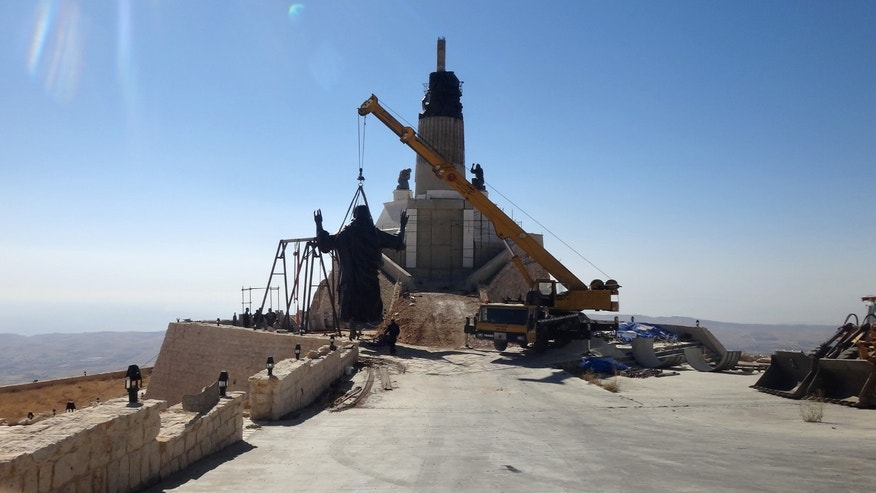 Oct. 14, 2013: This photo provided by the St. Paul's and St. George's Foundation shows workers preparing to install a statue of Jesus on Mount Sednaya, Syria.