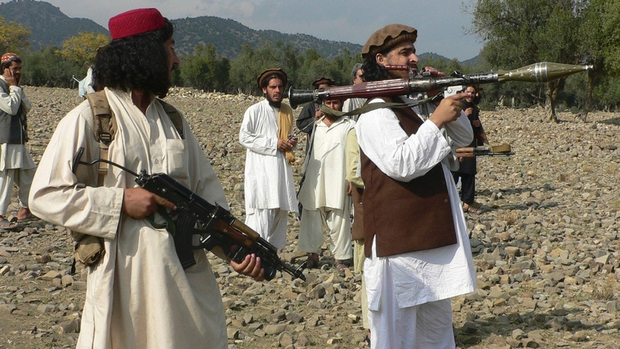 FILE -  In this Sunday, Oct. 4, 2009 file photo, Pakistani Taliban chief Hakimullah Mehsud,  right, holds a rocket launcher with his comrades in Sararogha of Pakistani tribal area of South Waziristan along the Afghanistan border. Intelligence officials said Friday, Nov. 1, 2013 that the leader of the Pakistani Taliban Hakimullah Mehsud was one of three people killed in a U.S. drone strike. (AP Photo/Ishtiaq Mehsud, File)