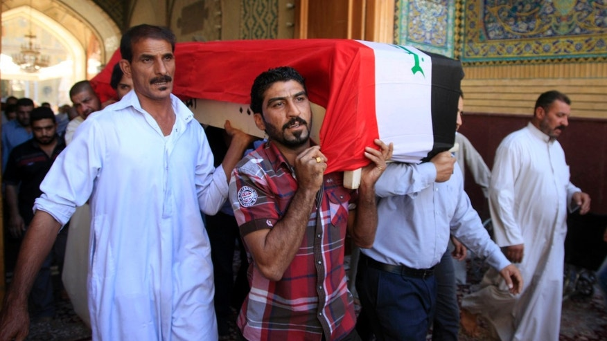 FILE - In this file photo taken on Oct. 21, 2013, mourners carry the coffin of a man killed in a bomb attack during a funeral in the Shiite holy city of Najaf, Iraq. The United Nations says that 979 Iraqis died in attacks in October, a monthly death toll that is exactly the same as the figure for September. (AP Photo/Jaber al-Helo, File)