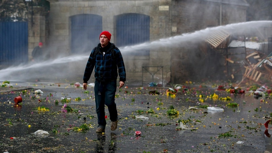 "Riot police use water canons to disperse protesters during clashes in Quimper, western France, Saturday, Nov. 2nd, 2013. Police and demonstrators, demanding jobs and a definitive end to an ""eco-tax"", skirmished ahead of a protest march by at least 10,000 people in the Breton city of Quimper. Protesters threw stones at police who responded with water cannon and tear gas ahead of Saturday's march which was held to send a strong message to the French government, which recently suspended the eco-tax, paid by trucks, for the western region of Brittany. (AP Photo/Gween Saliou)"