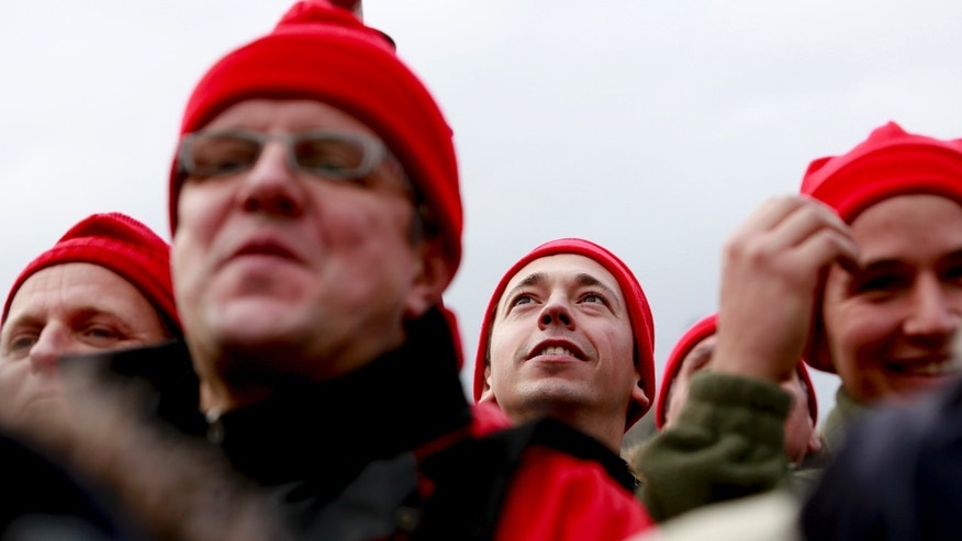 "Protesters, clad in red caps reminiscent of 17th century protests, take the streets to demonstrate against job losses and a controversial environment tax in Quimper, western France, Saturday, Nov. 2nd, 2013. Police and demonstrators, demanding jobs and a definitive end to an ""eco-tax"", skirmished ahead of a protest march by at least 10,000 people in the Breton city of Quimper. Protesters threw stones at police who responded with water cannon and tear gas ahead of Saturday's march which was held to send a strong message to the French government, which recently suspended the eco-tax, paid by trucks, for the western region of Brittany. (AP Photo/Gween Saliou)"