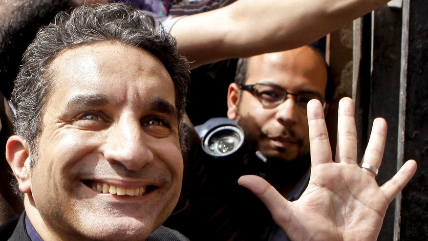 FILE - In this Sunday, March 31, 2013 file photo, Egyptian television satirist Bassem Youssef, known as Egypt's Jon Stewart, waves to his supporters as he enters Egypt's state prosecutors office to face charges  for allegedly insulting Islam and the country's leader, in Cairo, Egypt. Egypt's top prosecutor has ordered an investigation into a complaint that alleges  Youssef, harmed national interests by ridiculing the country's military. (AP Photo/Amr Nabil, File)