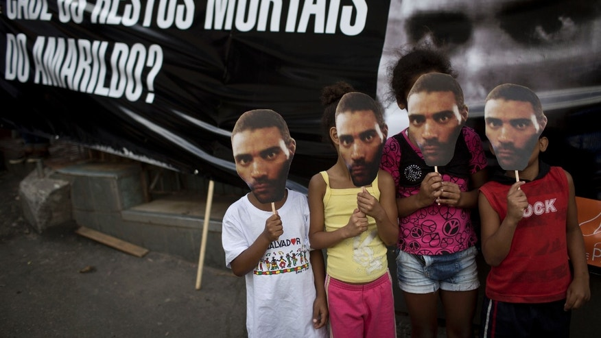 Young demonstrators pose for photos while covering their faces with a photo of Amarildo de Souza, next to a banner that reads 'Where are Amarildo's mortal remains?' during a protest in Rio de Janeiro, Brazil, Saturday, Nov. 2, 2013. Bricklayer Amarildo de Souza was last seen June 14 when police picked him up for questioning in Rio de Janeiro's Rocinha slum. (AP Photo/Felipe Dana)