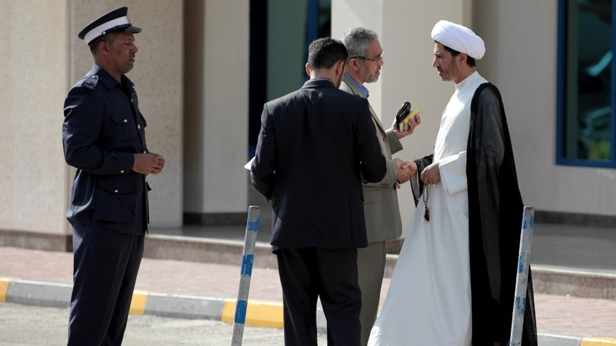 "Sheik Ali Salman, right, leader of the largest Shiite opposition group, the Al Wefaq Society, arrives with aides in response to a summons for questioning at the public prosecutor's office on Sunday, Nov. 3, 2013. The Bahraini government issued a statement accusing Salman of ""denigrating and disparaging the Interior Ministry"" through his society's museum-style exhibition of scenes from the 2 1/2-year-old pro-democracy uprising that police shut down last week. (AP Photo/Hasan Jamali)"