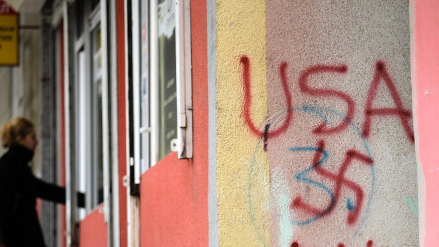 A women passes by graffiti that compares the USA to the Nazi swastika and EU, in the northern, Serb-dominated part of Mitrovica, Kosovo Saturday, Nov 2, 2013. Kosovo local elections are scheduled for November 3. As part of attempts to normalize its relations with Kosovo, Serbia has agreed to convince Kosovo Serbs to end their boycott of ethnic Albanian dominated institutions in protest over Kosovo's 2008 secession from Serbia. Serbia claims the territory as its own. (AP Photo/Darko Vojinovic)